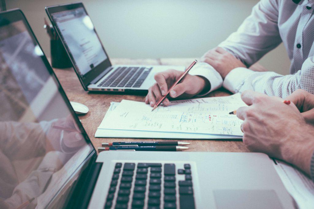 Deux personnes travaillent en équipe avec du papier et leurs ordinateurs respectifs